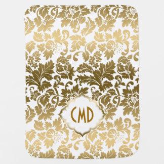 El oro entona los damascos florales sobre el fondo mantas de bebé