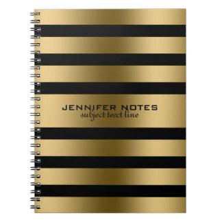 El oro metálico raya el fondo negro libro de apuntes con espiral