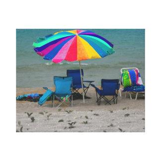 el parasol de playa colorido preside la escena de  impresion de lienzo