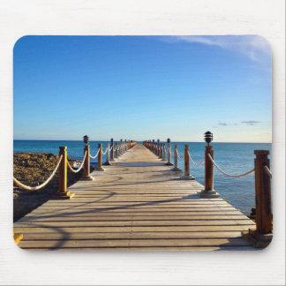 El paseo marítimo de madera extiende sobre el agua mouse pad