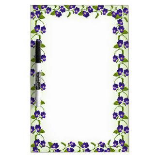 El pensamiento púrpura de la viola florece al tabl tablero blanco