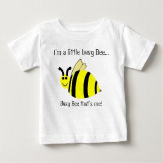 El pequeño amarillo de la abeja ocupada manosea la remeras
