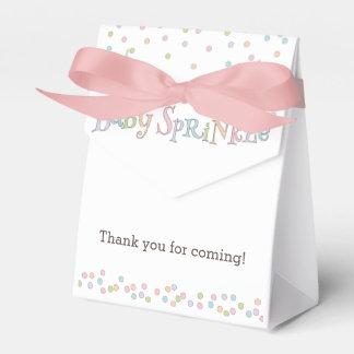 El pequeño bebé asperja el bolso del favor de la caja para regalos de fiestas