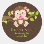 El pequeño chica lindo del mono le agradece pegatina redonda