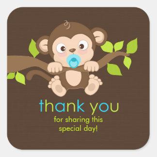 El pequeño muchacho lindo del mono le agradece pegatina cuadrada