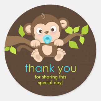 El pequeño muchacho lindo del mono le agradece pegatina redonda
