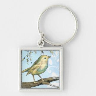 El pequeño pájaro amarillo se encaramó en una rama llavero cuadrado plateado