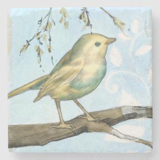El pequeño pájaro amarillo se encaramó en una rama posavasos de piedra