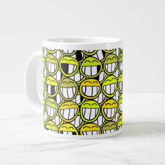 El pequeño smiley amarillo divertido hace frente a taza de café grande