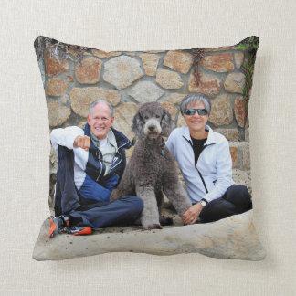El perro de caniche estándar gris goza de la playa cojines