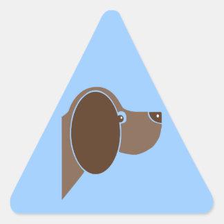 El perro persigue el animal lindo del dibujo pegatina triangular