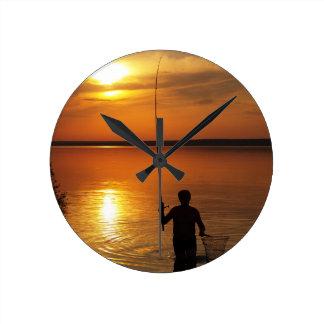 El pescador coge pescados haciendo girar reloj redondo mediano