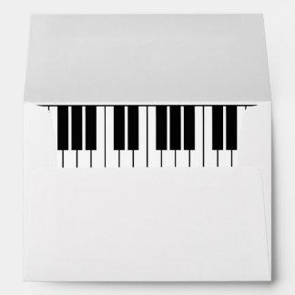 El piano blanco y negro cierra envlopes del sobre