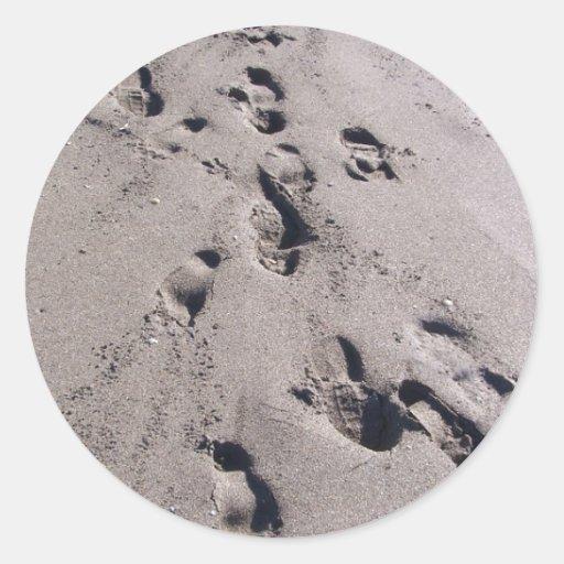 El pie imprime en arena mojada de la playa hacia e etiqueta
