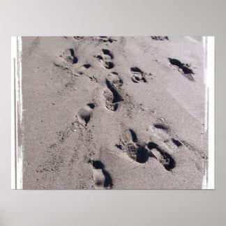 El pie imprime en arena mojada de la playa hacia e póster