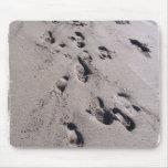 El pie imprime en arena mojada de la playa hacia e tapete de ratón