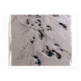 El pie imprime en arena mojada de la playa hacia postal