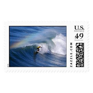 El practicar surf bajo franqueo del arco iris