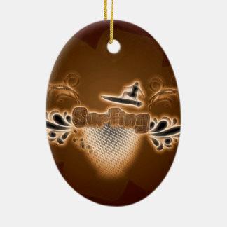 El practicar surf, surfboarder con los elementos adorno navideño ovalado de cerámica