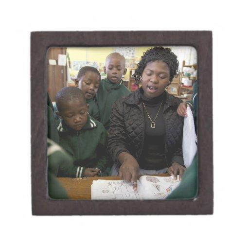 El profesor ayuda a un grupo del principiante en caja de regalo de calidad