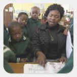 El profesor ayuda a un grupo del principiante en pegatinas cuadradas