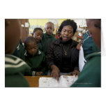 El profesor ayuda a un grupo del principiante en tarjetón