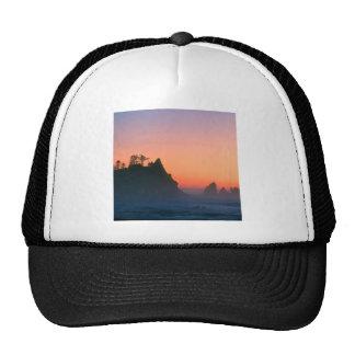 El punto de la puesta del sol arquea pilas del mar gorros