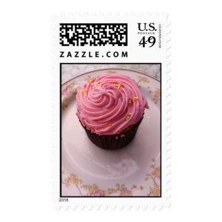 El rosa helado asperja la magdalena en una placa envio