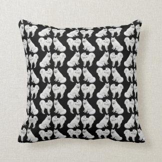 El samoyedo blanco amistoso persigue la almohada