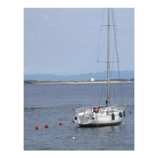 El solo velero miente en el ancla en un puerto membrete personalizado