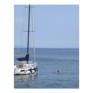 El solo velero miente en el ancla en un puerto plantilla de membrete