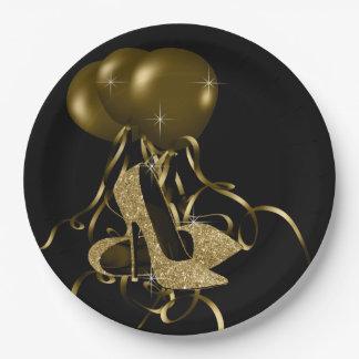 El tacón alto negro del brillo del oro calza el platos de papel