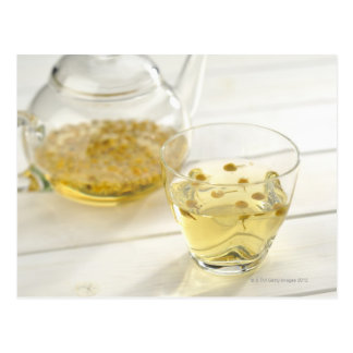 El té de hierba que una tetera de cristal y una tarjetas postales