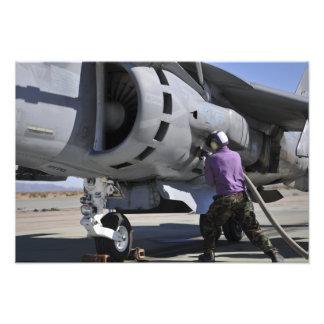 El técnico del combustible de aviación ata una fotografías
