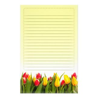 El tulipán amarillo rojo florece el fondo amarillo papelería