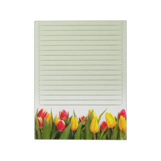 El tulipán amarillo rojo florece el fondo verde al bloc de papel