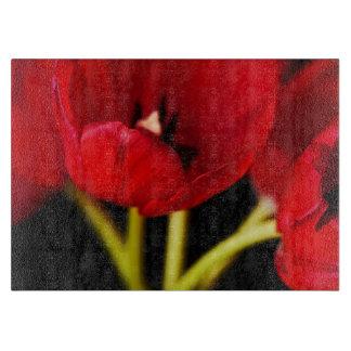 El tulipán rojo florece el fondo negro floral tabla para cortar