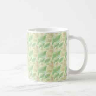 El verde suave hojea pequeño modelo en una taza
