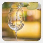 El vino blanco se vierte de la botella en pegatina cuadrada