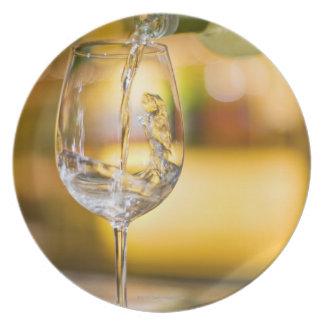 El vino blanco se vierte de la botella en plato para fiesta