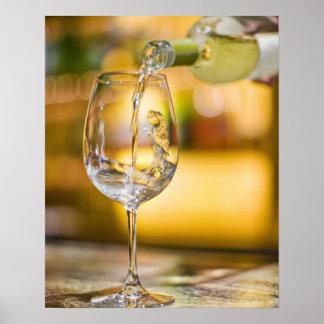 El vino blanco se vierte de la botella en restaura posters