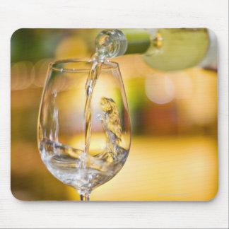 El vino blanco se vierte de la botella en restaura tapete de ratón