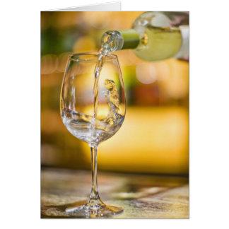 El vino blanco se vierte de la botella en restaura tarjeta de felicitación