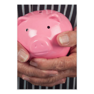 Elderly hand holding piggy bank card