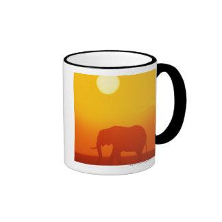 Elefante africano que camina en la puesta del sol, tazas