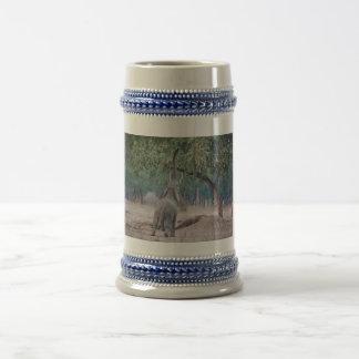Elefante que alcanza para el árbol del acacia jarra de cerveza
