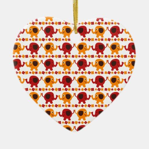 Elefantes rojos y anaranjados lindos que sostienen adorno de cerámica en forma de corazón