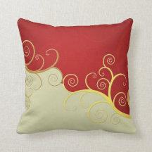 Elegant golden swirls on red and cream pillows