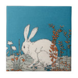 """Elegant Vintage White Rabbit Ceramic Tile<br><div class=""""desc"""">This is a vintage illustration of a white rabbit.  He is sitting in a patch of grass and flowers.  Elegant color scheme of blue,  gray and orange.  See my store Art by MAR for matching products with this design.</div>"""
