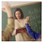 Elementary school students raising their hands ceramic tile